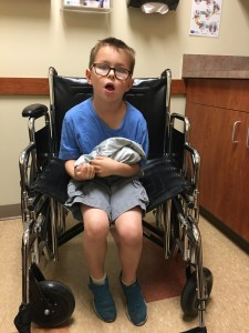 At the urgent care - I was lifting him everywhere but it was hurting my back, so our hero got to ride in a wheelchair, which thrilled him to no end.