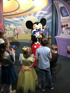 Mickey autographs while charmed kiddos look on with wonder